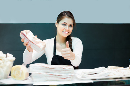 shopgirl: Female butcher with salty lard in counter of meat store Stock Photo