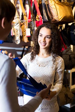 shopgirl: Smiling female shopgirl helping young man to select handbag in store