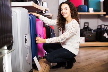 haberdashery: Young happy woman choosing travel suitcase in haberdashery shop