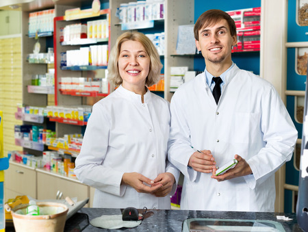 farmacy: Portrait of two pleasant smiling pharmacists working in modern farmacy