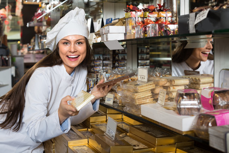 shopgirl: Young shopgirl posing with delicious chocolate and confectionery at supermarket Stock Photo