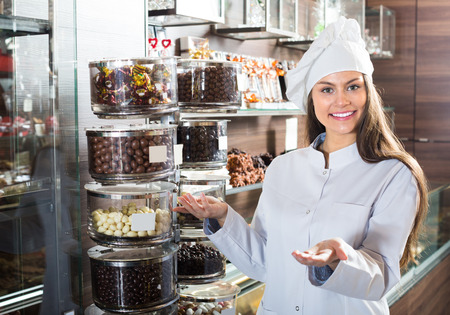 shopgirl: Young shopgirl posing with delicious chocolate and confectionery at coffee-house