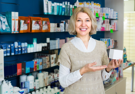 50 to 60: Smiling mature female patient in pharmacy drugstore