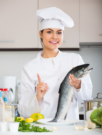 corcovado: Young chef holding carcass of fish in professional kitchen