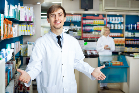 farmacy: Portrait of two friendly cheerful pharmacists working in modern farmacy Stock Photo