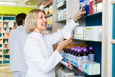 60 65: Smiling female technician working in chemist shop