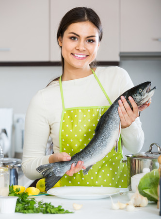 25 35: Pretty european girl holding rainbow trout in domestic kitchen
