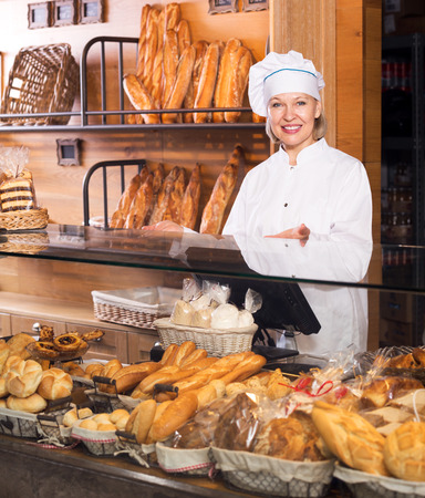 45 50: Happy senior woman selling fresh pastry and baguettes in local bakery