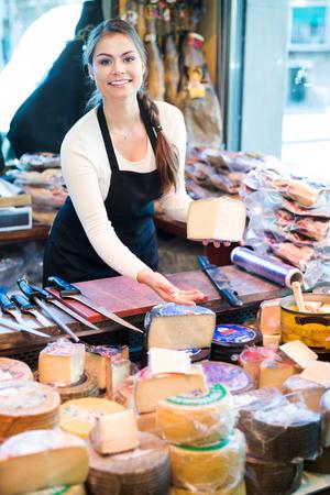 shopgirl: Cheerful young shopgirl selling cheese in a delicatessen store