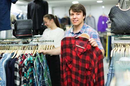 Young smiling man choosing shirt at the clothing store