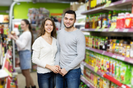 canned goods: Portrait happy couple standing near shelves with canned goods at shop Stock Photo