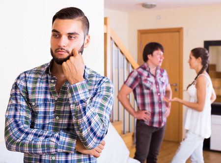 bisexual women: Sad guy and young couple at home: problems of love triangle