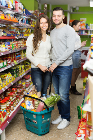 canned goods: Young smiling people standing near shelves with canned goods at shop