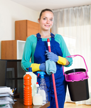 charwoman: happy professional young cleaner  cleaning the office