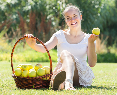 spanish girl: Happy spanish girl with apples harvest in garden