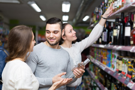 vodka bottle: Cheerful young adults standing at alcohol section and checking vodka bottle. Focus on guy