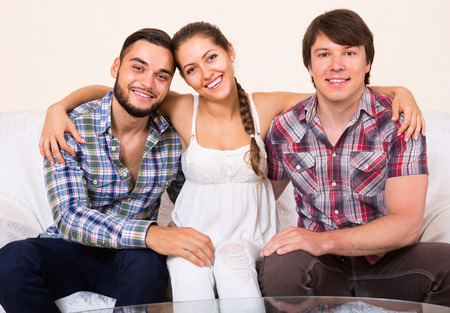 polygamy: Portrait of happy young smiling polygamous family posing at home Stock Photo