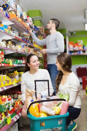 tinned: Adults choosing tinned food at supermarket