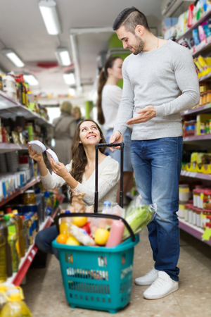 canned goods: happy european customers standing near shelves with canned goods at shop Stock Photo
