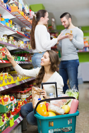 tinned: Positive adults choosing tinned food at supermarket Stock Photo