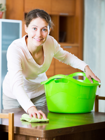 clean up: Positive european housewife doing regular clean up in living room