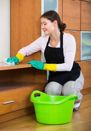 dusting: Smiling young woman in apron and rubber gloves dusting furniture at domestic interior