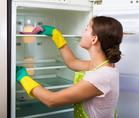 regular people: Young housewife cleaning refrigerator inside and smiling