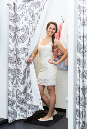 cubicle: Beautiful brunette girl standing at boutique changing cubicle Stock Photo