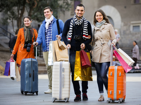 25 35: Two couples of young travellers with shopping bags and luggage on city street. Selective focus