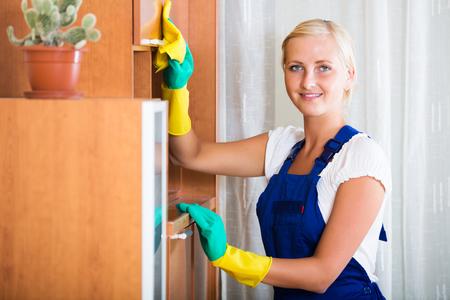 25 35: Professional smiling female cleaner doing regular clean-up in livingroom Stock Photo