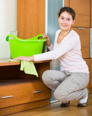 25 35: Cheerful caucasian woman cleaning at home with smile on face