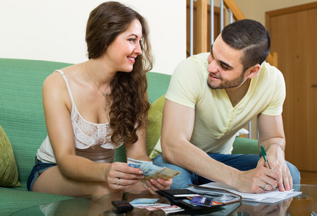 ruminate: Smiling young married couple calculating the family budget in living room