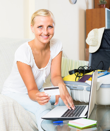 25 30: blonde with packed suitcase booking hotel for vacation online