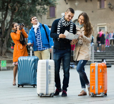 group direction: Group of friends with a luggage checking direction in the map outdoor