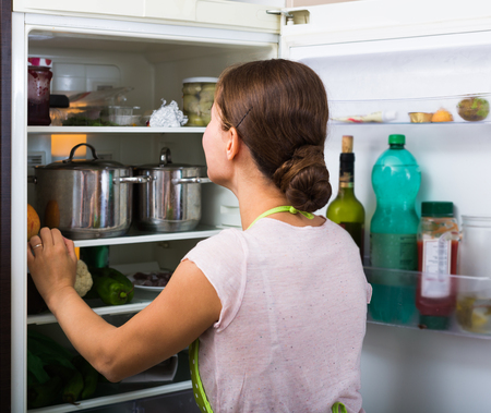 spanish looking: Adult spanish brunette in apron looking at products in refrigerator