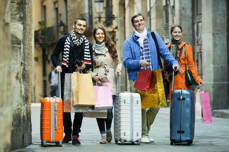 25 35: Group of young smiling tourists walking through European town and carrying shopping bags