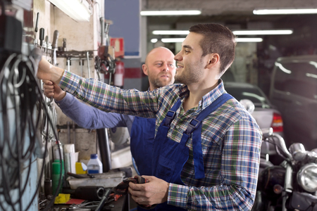 motor mechanic: Happy two men in coveralls working at auto repair shop