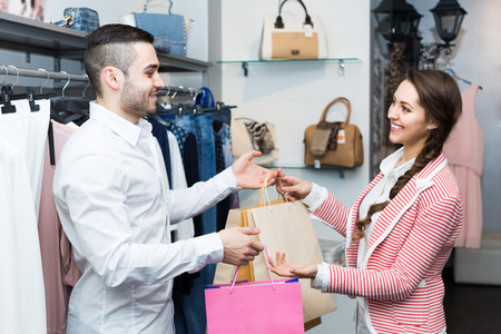 customer focus: Smiling customer with cheerful female shop assistant at boutique. Focus on man Stock Photo