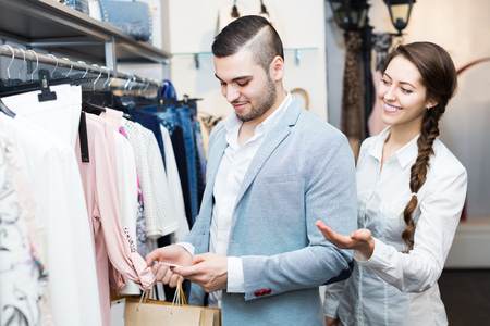 Positive young store clerk serving purchaser at fashionable apparel store Stock Photo