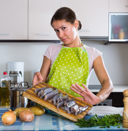 the stinking: Housewife in apron wincing of disgusting smell of fish