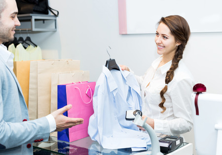 satisfied customer: Smiling cashier and satisfied customer at checkout desk Stock Photo