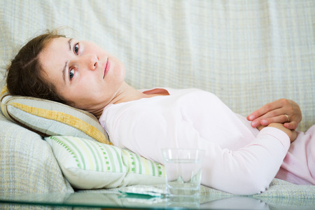 early pregnancy: Portrait of american girl folding up with belly pain indoor