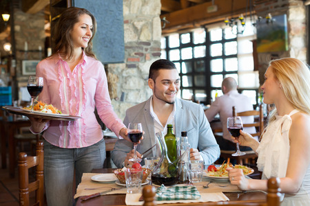 respectful: Portrait of relaxed adults people having dinner and respectful waiter