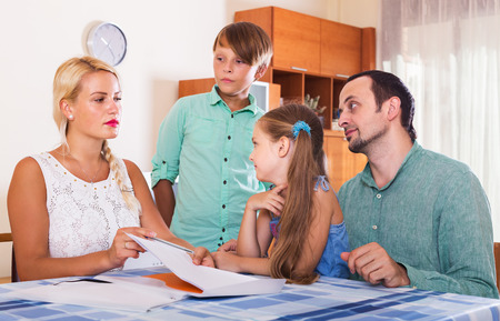 inspector kid: Parent with boy and girl making customer complaints at office interior. Focus on woman Stock Photo