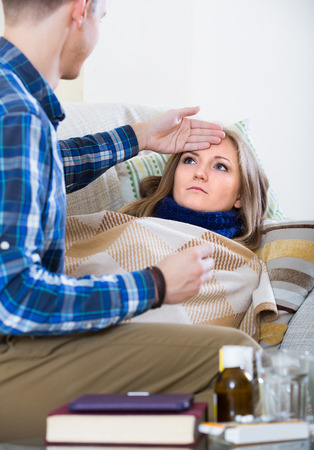 taking a wife: Young american woman with cold lying on couch, boyfriend taking care