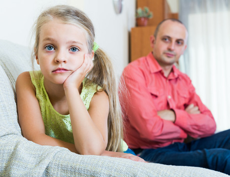 30 35: Serious dad and offended little girl quarrelling indoors. focus on girl