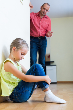 40 45: Adult man lecturing unpleased little daughter in home interior Stock Photo