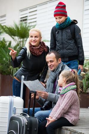 clase media: familia de clase media de cuatro miembros feliz direcci�n de verificaci�n en el mapa al aire libre Foto de archivo