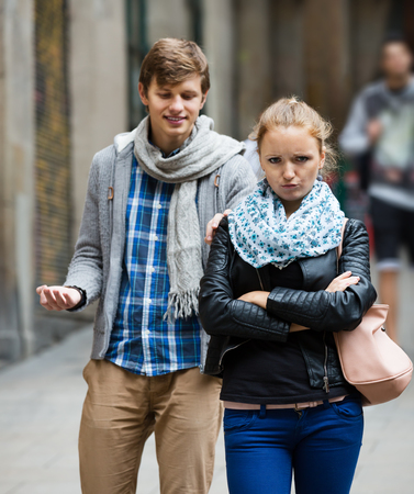 unwelcome: Young couple having quarrel on city street in the autumn day Stock Photo