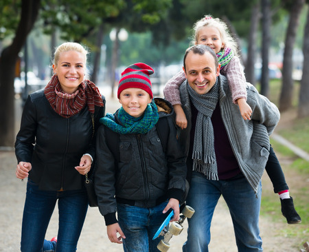 2 november: Portrait of happy parents with school age children spending time together outdoors
